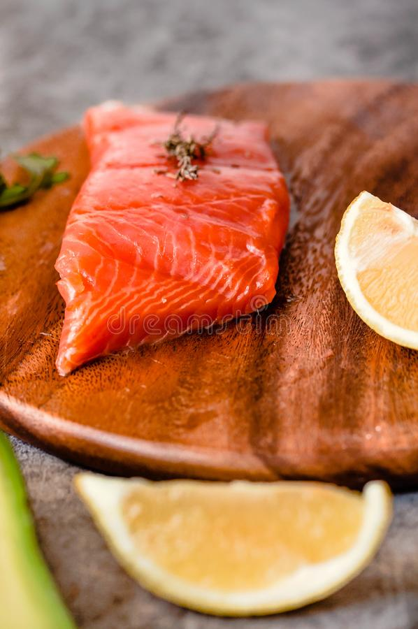 Portion of wild salmon fillet with aromatic herbs, spices, avocado and lemon- healthy breackfast, diet, omega 3 concept royalty free stock images