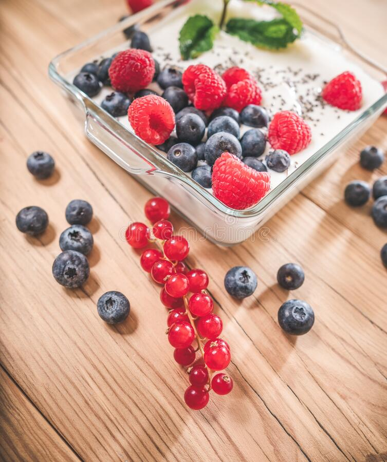 Portion of yogurt with berries serving in glass bowl royalty free stock image