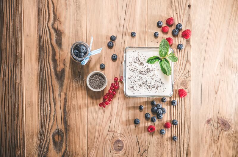 Portion of yogurt with berries serving in glass bowl stock image