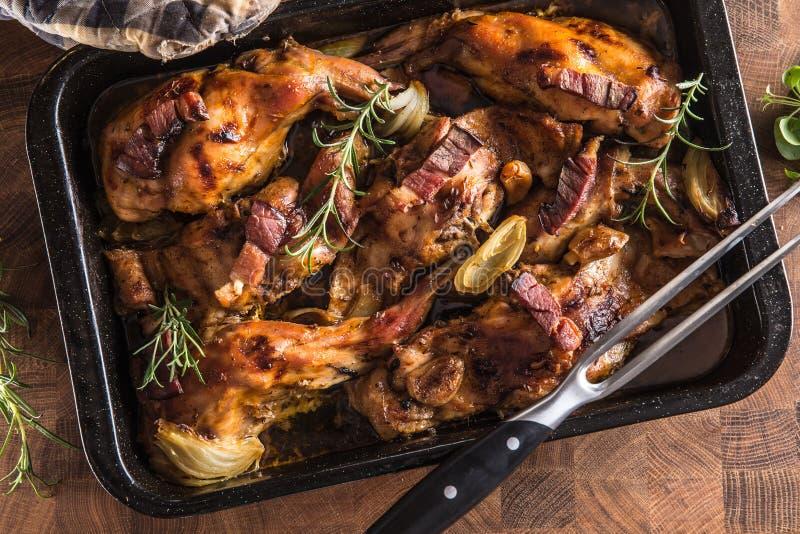 Portioned烘烤了在一个平底锅的兔子用葱迷迭香和调味汁 图库摄影