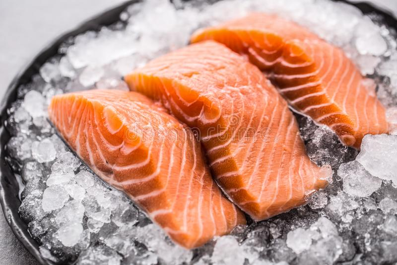 Portioned raw salmon fillets in ice on plate - Close-up.  royalty free stock image
