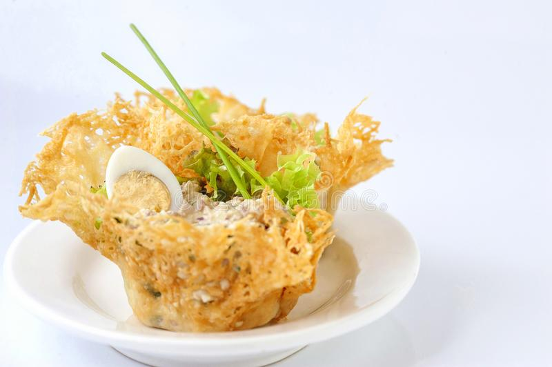Portioned snack in baked crispy cheese tartlet. Close up and horizontal view royalty free stock photos