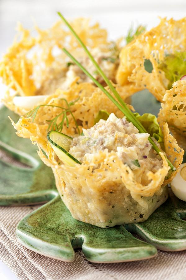 Portioned snack in baked crispy cheese tartlet. Close up and vertical view stock photo