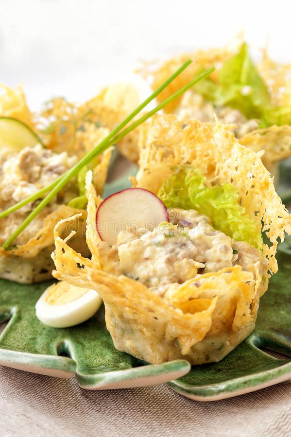 Portioned snack in baked crispy cheese tartlet. Close up and vertical view stock photography