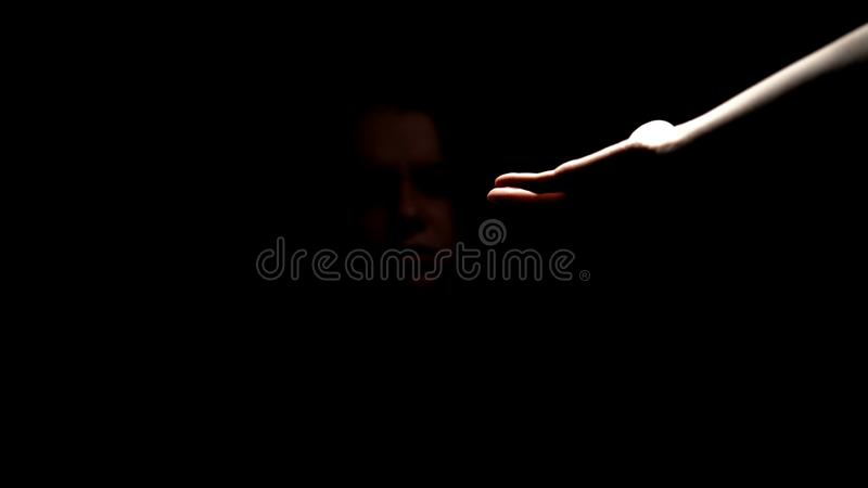 Portionhand som ger service till den deprimerade övergav kvinnan i mörker, hjälpmedel royaltyfria bilder