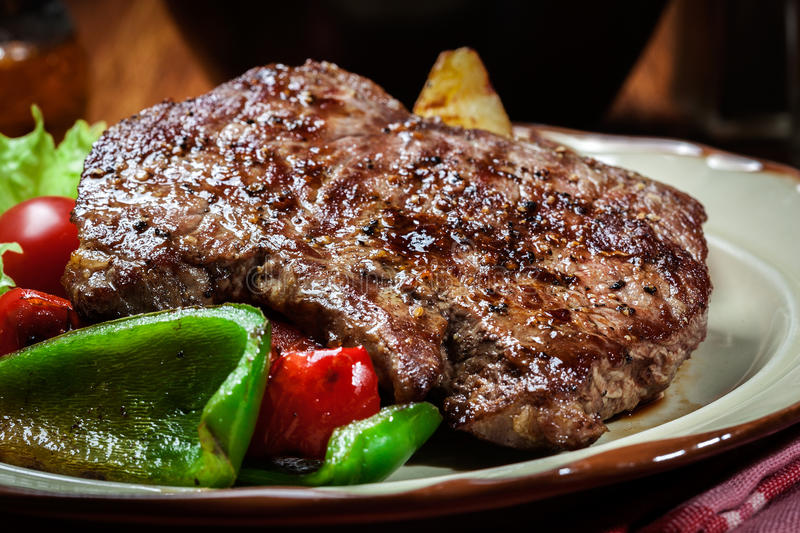 Portions of grilled beef steak with grilled potatoes and paprika. Portions of grilled beef steak served with grilled potatoes and paprika stock image