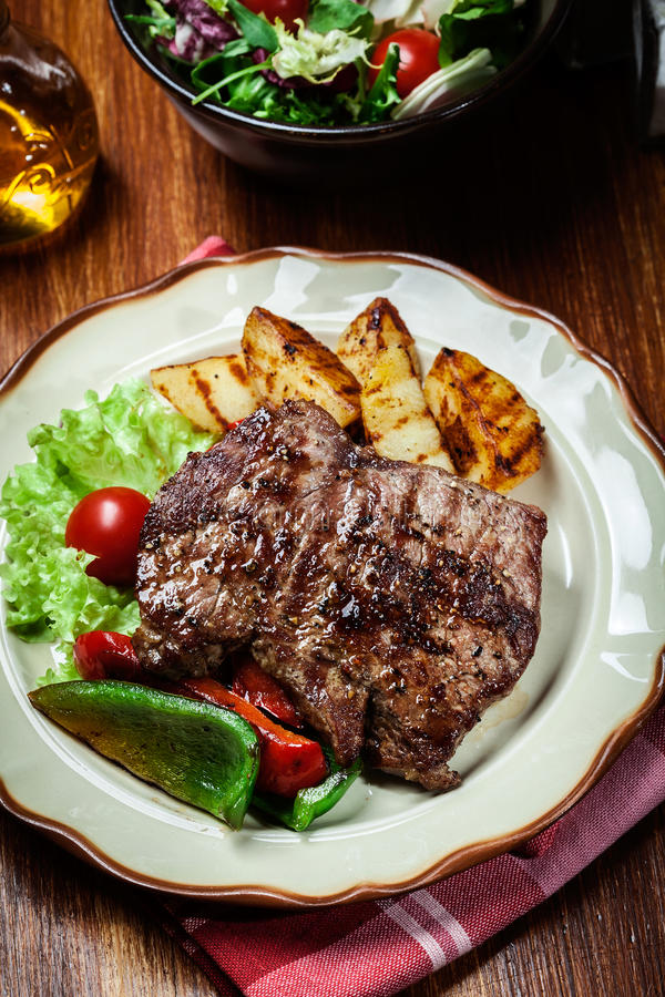Portions of grilled beef steak with grilled potatoes and paprika. Portions of grilled beef steak served with grilled potatoes and paprika royalty free stock image