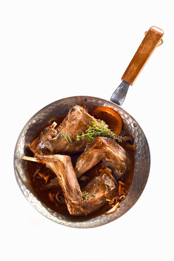 Portions of roasted wild rabbit with mushrooms. Portions of roasted wild rabbit venison with mushrooms and fresh thyme or oregano served in a rich gravy in a pan royalty free stock photo