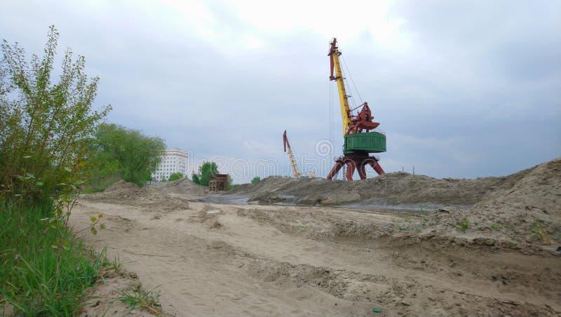Portkranar på spillroravlastningen Gamla lastningsbryggakranar och berg av sand arkivbilder