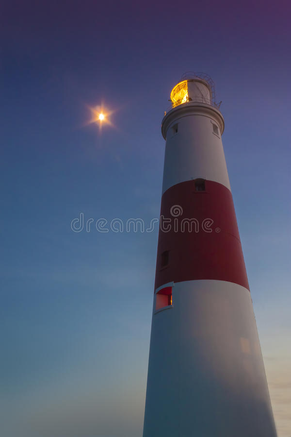 Portland Bill Lighthouse at dusk. The moon climbs up behind Portland Bill lighthouse just as the last rays of the sun hit the tower royalty free stock photos