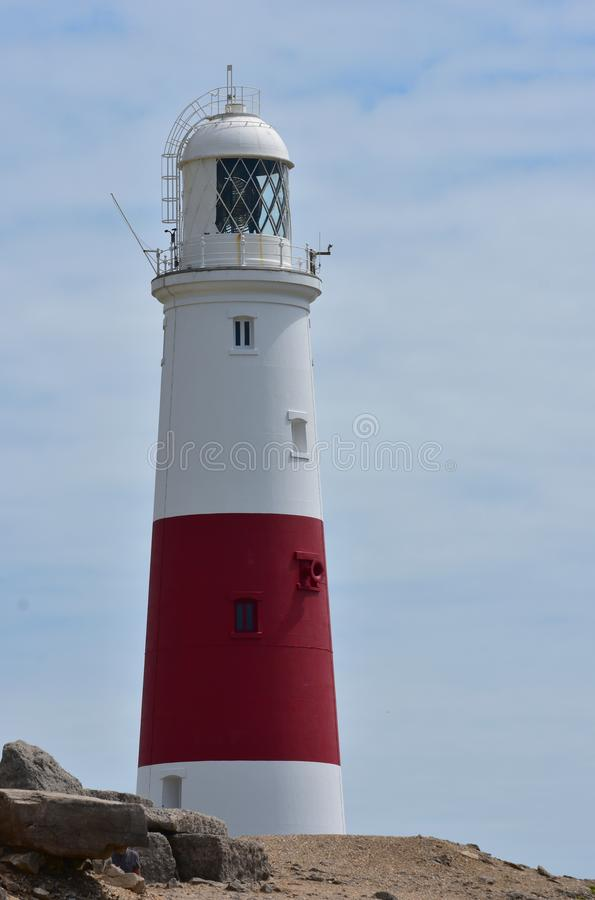 Portland Bill Lighthouse. Sunny, sky, red, white, tall, warning, rocks, coast, coastline, beacon, bright, sea, shore, cliffs, rocky, ship, ships, shipping stock image