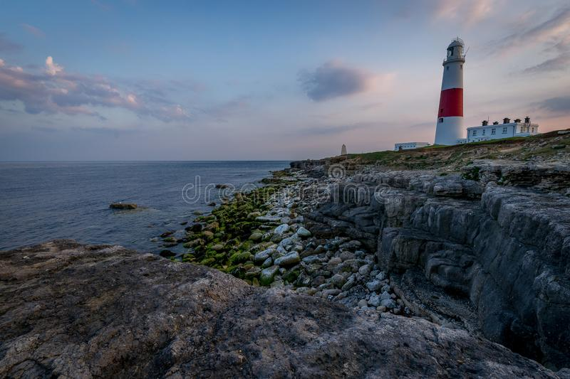 PORTLAND BILL LIGHTHOUSE AT SUNSET IN DORSET. WITH A ROCKY FOREGROUND AND KEEPING THE SHIPS SAFE royalty free stock images