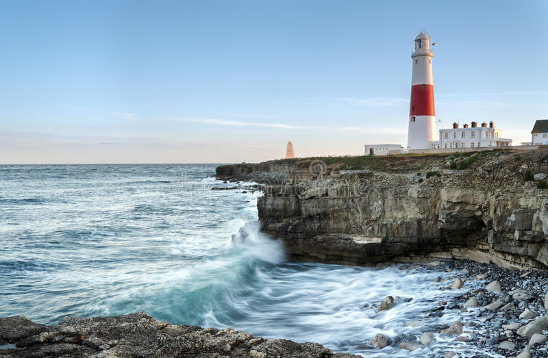 Portland Bill Lighthouse. Waves crashing over rocks at Portland Bill lighthouse on the Jurassic Coast in Dorset stock image