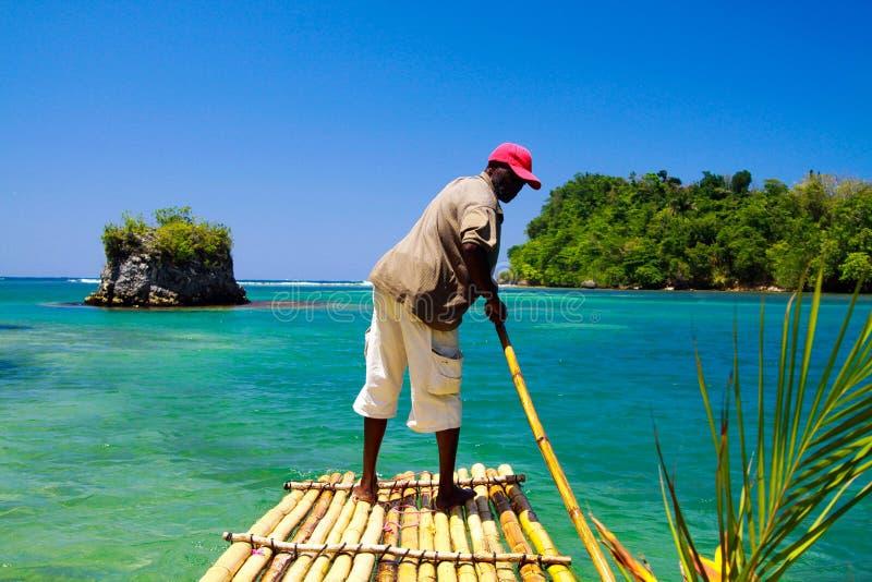PORTLAND BLÅ LAGUN, JAMAICA - MAJ 22 2010: Sväva på den enkla bambuflotten in i den blåa lagun arkivbild