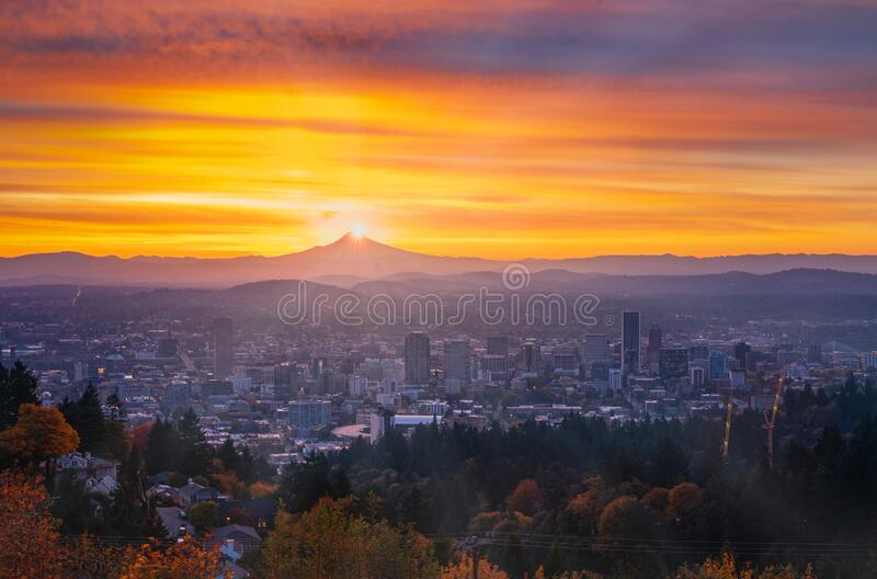 Portland downtown with  autumn foliage in thin fog, shining sunrise and colorful clouds. Photograph of Portland downtown with  autumn foliage in thin fog royalty free stock photography