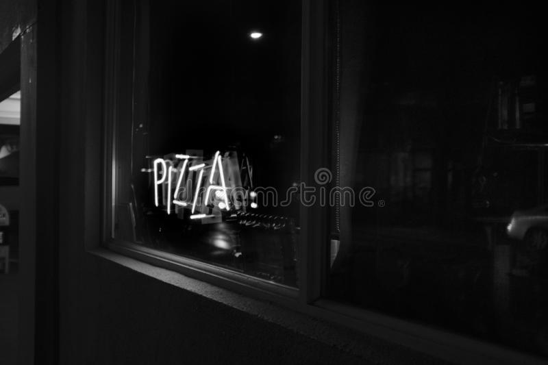 Grey scale shot of the windows of a dark pizza parlor captured in Portland, United States. PORTLAND, UNITED STATES - Nov 23, 2019: A grey scale shot of the stock photos