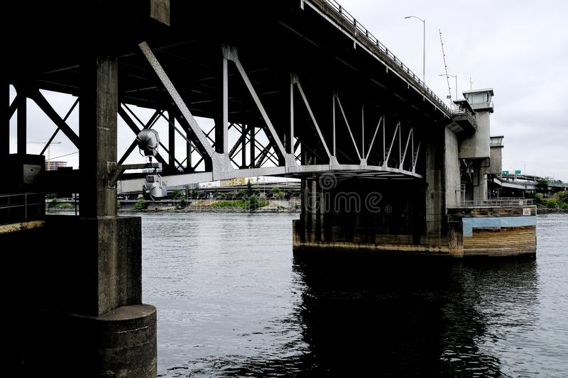 Metal bridge going over the calm river in Portland, United States. PORTLAND, UNITED STATES - Sep 07, 2019: A metal bridge going over the calm river in Portland stock images