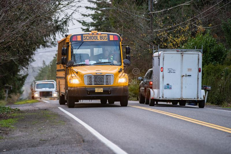Yellow school bus driving on a street royalty free stock photo