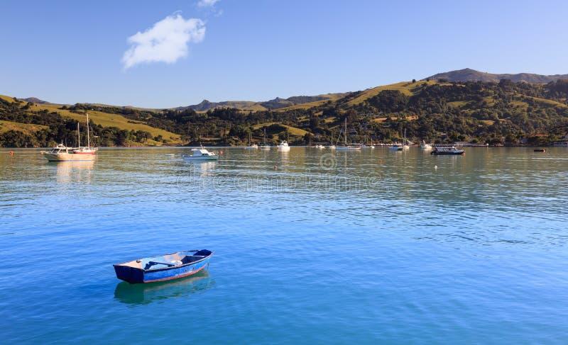 Porto azul vazio de Akaroa do barco de enfileiramento foto de stock