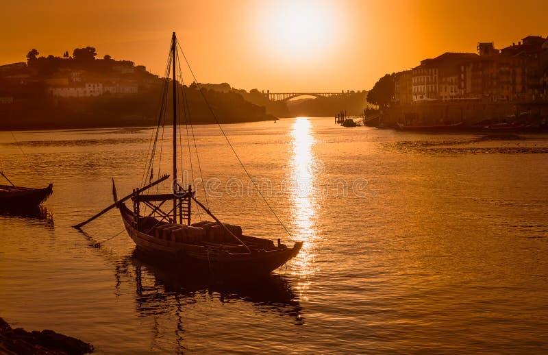 Porto bei Sonnenuntergang: Duoro-Fluss mit rabelo Boot vor untergehender Sonne und Arrabida-Brücke im Hintergrund, Portugal stockfoto