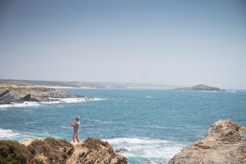 Porto Covo, Portugal - um homem não identificado toma um selfie sobre um penhasco da praia do dos Buizinhos do praia foto de stock royalty free