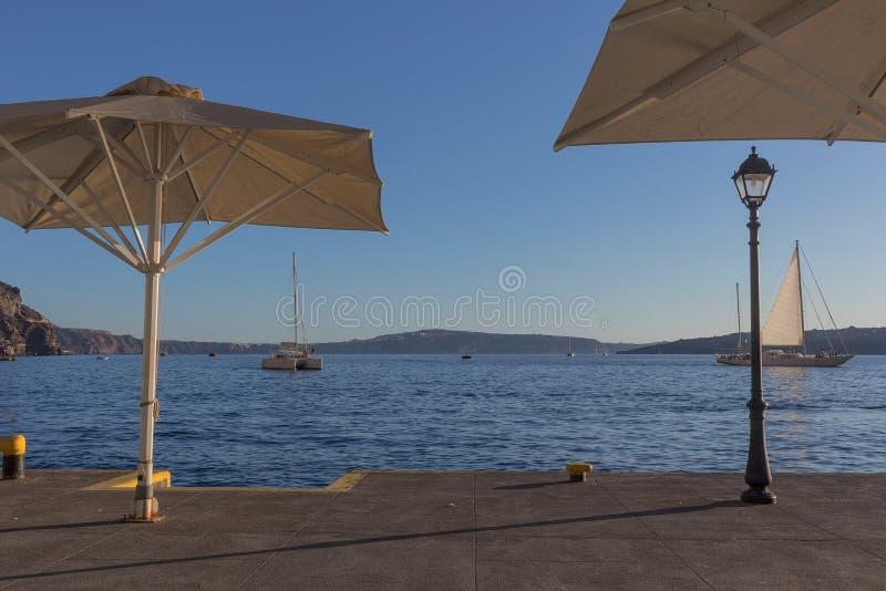 Porto de Fira com os barcos no por do sol Santorini, Greece imagem de stock