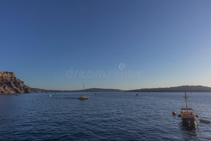 Porto de Fira com os barcos no por do sol Santorini, Greece fotos de stock royalty free