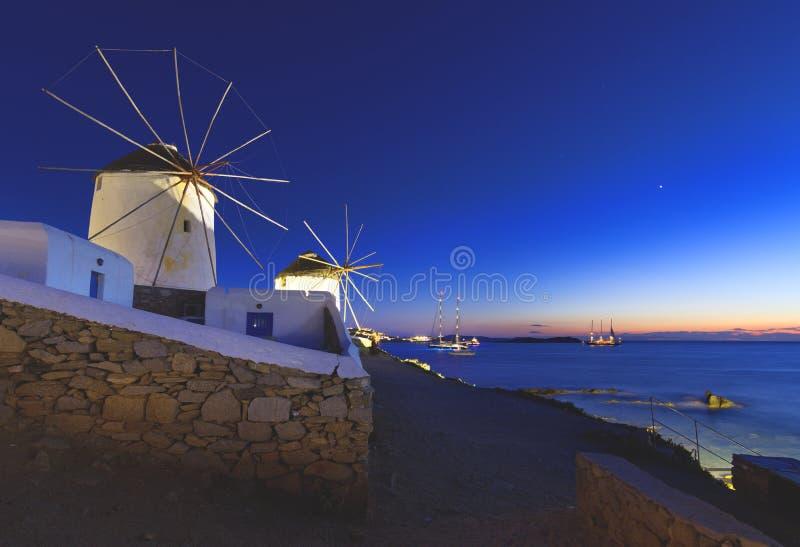 Porto de Mykonos com barcos e moinhos de vento na noite, ilhas de Cyclades, Grécia imagem de stock royalty free