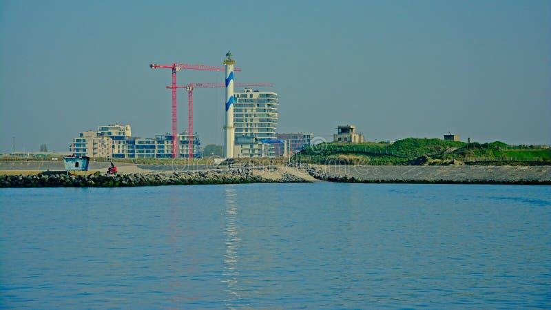 Porto de Ostende, Bélgica com as dunas com ruínas do depósito, farol e prédios de apartamentos novos sob construções imagens de stock