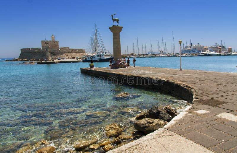 Porto de Rhodes Mandraki com castelo e as estátuas simbólicas dos cervos, Grécia fotografia de stock royalty free