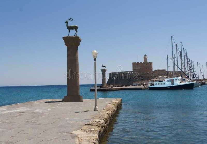 Porto de Rhodes Mandraki com castelo e as estátuas simbólicas dos cervos, Grécia imagens de stock