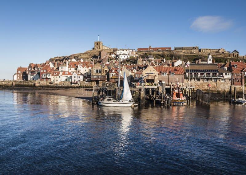 Porto de Whitby em um dia claro que mostra o cais e a igreja no monte imagem de stock