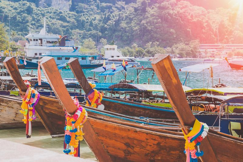 Porto dell'isola tropicale con i crogioli di legno attraccati di coda lunga del taxi e dei fishermans domestici Montagne su fondo immagine stock libera da diritti
