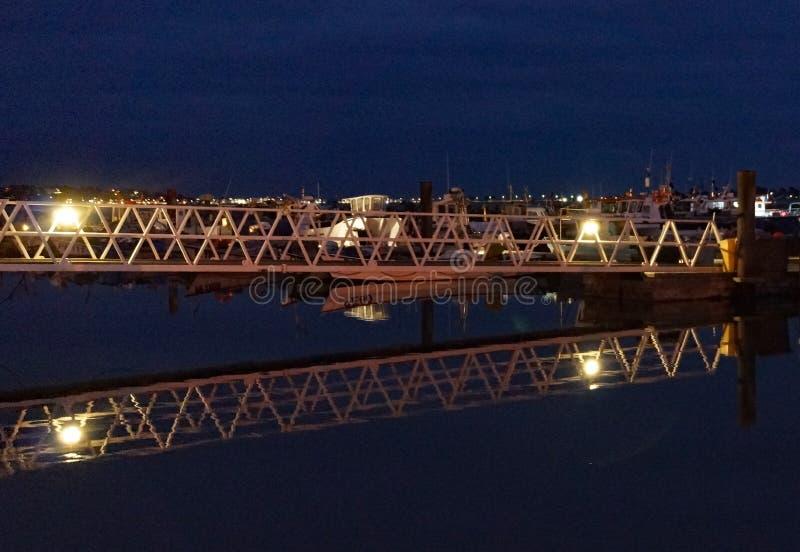 Porto di Poole alla notte con i pescherecci attraccati sul pontone, con un passaggio pedonale a acce fotografia stock