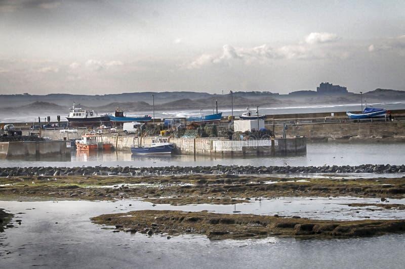 Porto di Seahouses in Northumberland con il castello di Bamburgh fotografie stock