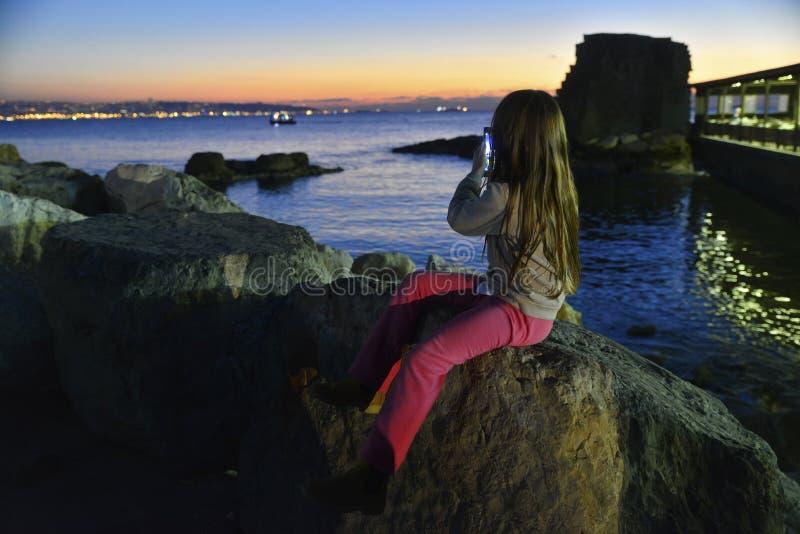 Porto do acre do fotógrafo da criança no por do sol fotos de stock royalty free