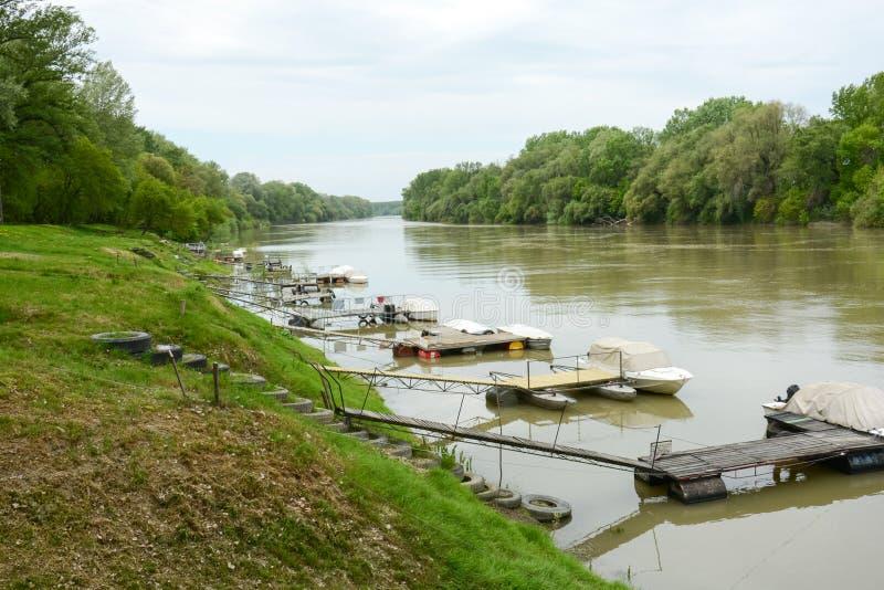 Porto do bote no rio com cais e escadas do pneumático imagens de stock royalty free