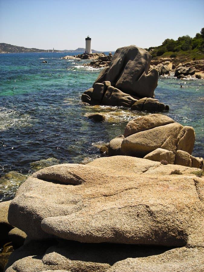Porto Faro. Stones in direction of Porto Faro with blue sea and lighthouse - Sardegna - Italy 2008 stock photo