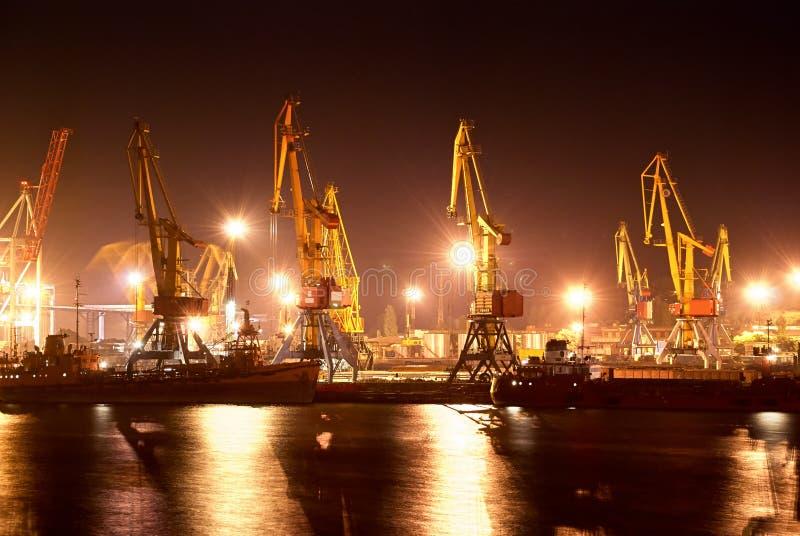 Porto industrial com os guindastes na noite imagens de stock royalty free