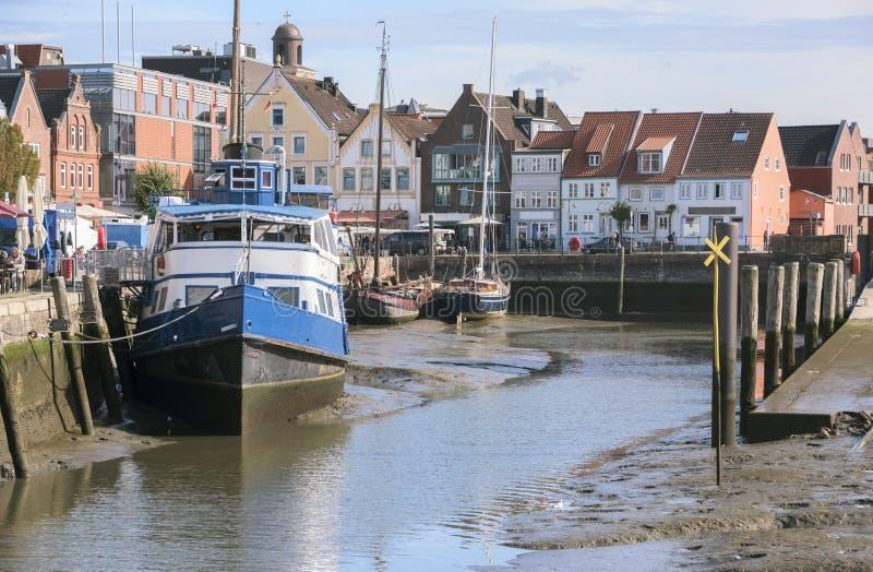 Porto interno a bassa marea nella vecchia città di Husum con le barche sopra fotografia stock