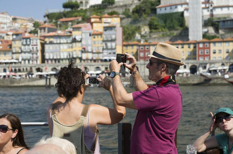 Porto, Portugal, August 21, 2018: an Italian couple takes pictures from a tourist boat on the phone of a tourist attraction in royalty free stock image