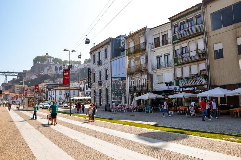 Porto, Portugal - August 31 2018: People walking on promenade by river Douro on a sunny day. The embankment is full of restaurants stock image