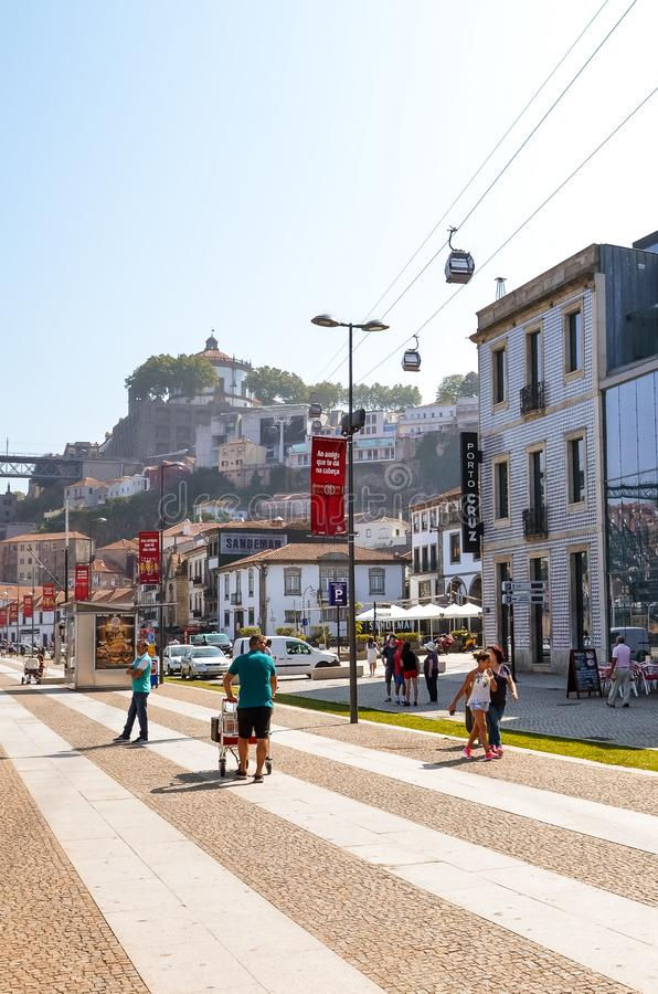 Porto, Portugal - August 31 2018: Tourists walking on promenade by river Douro on a sunny day. The embankment is full of royalty free stock photos