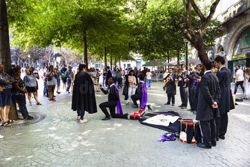 Porto, Portugal. August 12, 2017: Tuna from the University of Oporto singing to two women with two of the kneeling tunos declaring. Themselves to women and the royalty free stock photo