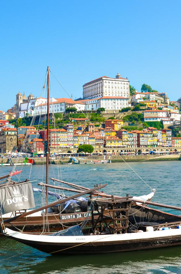 Porto, Portugal - August 31 2018: Vertical picture of traditional wooden boats used for wine barrel transport on river Douro. Historical center in background royalty free stock photo