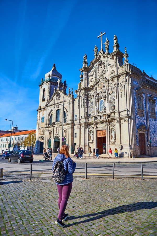 Porto, Portugal - 09 de dezembro de 2018: Turista da jovem mulher com posição portuguesa da bandeira perto da igreja de Congregad foto de stock royalty free