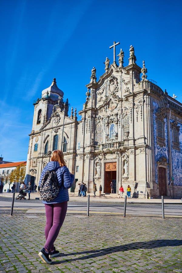 Porto, Portugal - 09 de dezembro de 2018: Turista da jovem mulher com posição portuguesa da bandeira perto da igreja de Congregad fotografia de stock royalty free