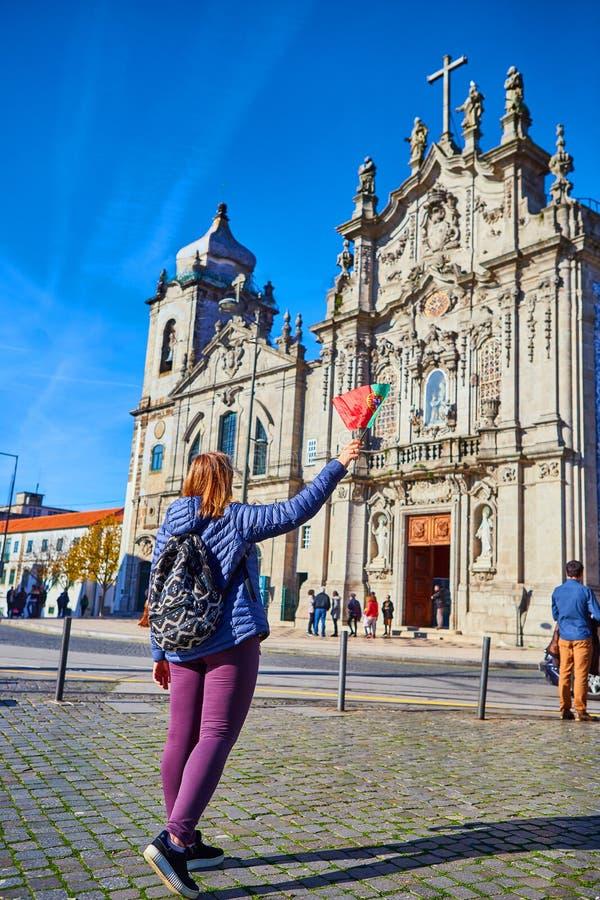 Porto, Portugal - 09 de dezembro de 2018: Turista da jovem mulher com posição portuguesa da bandeira perto da igreja de Congregad foto de stock
