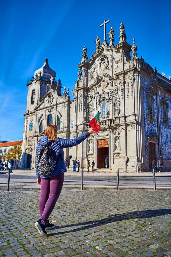 Porto, Portugal - 09 de dezembro de 2018: Turista da jovem mulher com posição portuguesa da bandeira perto da igreja de Congregad imagem de stock royalty free