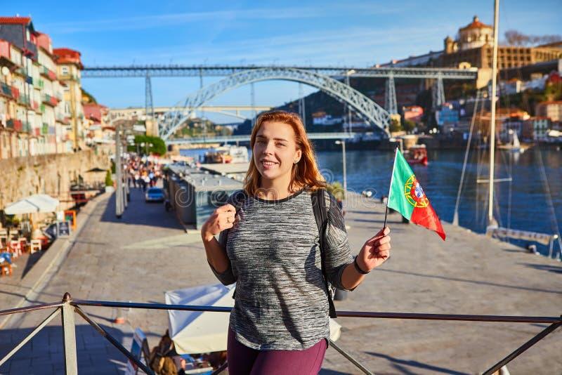 Porto, Portugal - 09 de dezembro de 2018: Viajante da jovem mulher que está para trás com a bandeira portuguesa, apreciando a arq imagens de stock